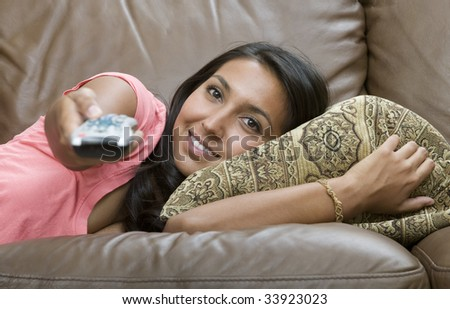 A young woman with remote control relaxing on sofa - stock photo