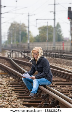 a young woman with suicide thoughts sitting on a track. holds farewell letter in his hand and thinks about her suicide after. - stock photo