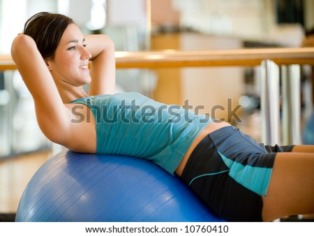 A young woman working out in a gym - stock photo