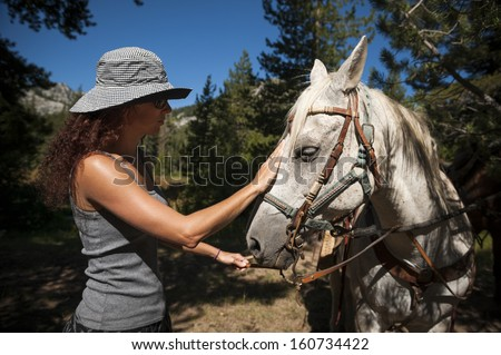 a young woman working with a white horse in the mountains - stock photo