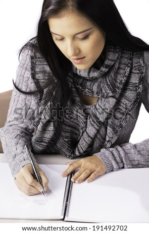 A young woman writes in a notebook.  - stock photo