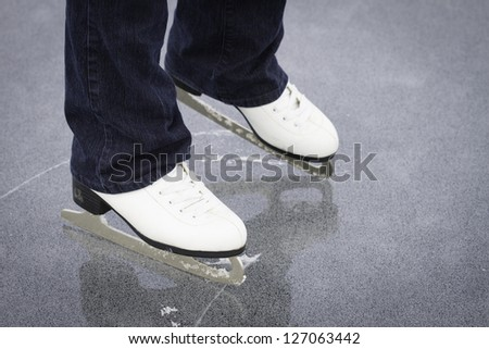 A young women's ice skates on a frozen pond in northern Maine - stock photo