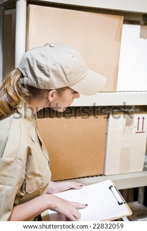 A young worker taking inventory in a warehouse - stock photo