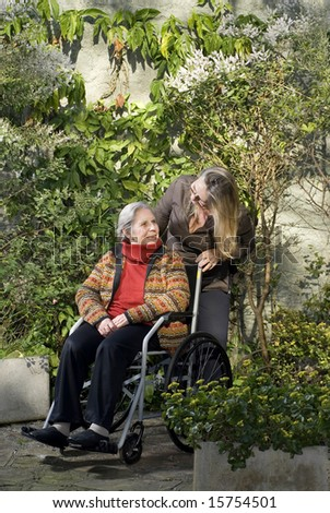 A younger woman is with her elderly mother in a garden.  She is pushing her wheelchair, smiling, and looking at the older woman who is looking away.  Vertically framed shot. - stock photo
