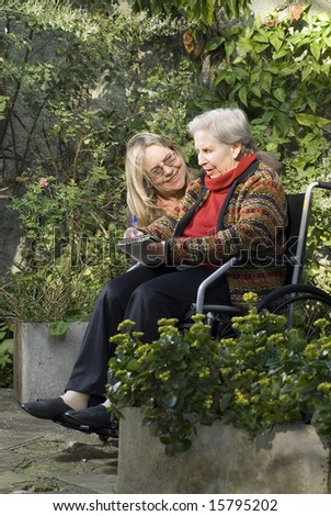 A younger woman is with her elderly mother in a garden.  The older woman is sitting in a wheelchair.  She is smiling at her mother who is looking away.  Vertically framed shot. - stock photo