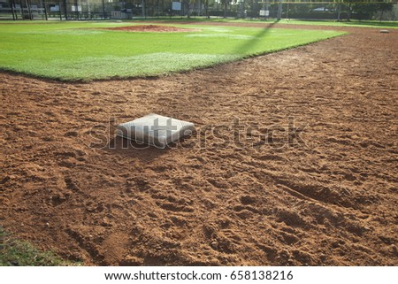 A youth baseball field infield with first base in the foreground
