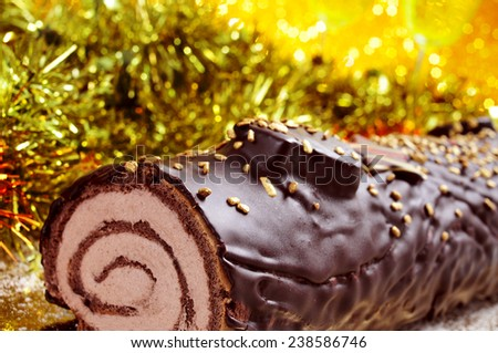 a yule log cake, traditional of christmas time, on a festive table ornamented with shiny tinsel - stock photo