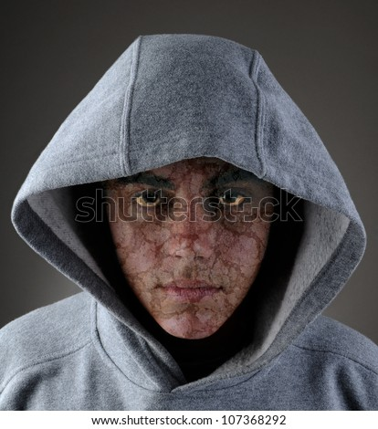 A zombie like teenage male in a gray hoodie.