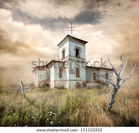 aAbandoned church near the cemetery in a field - stock photo