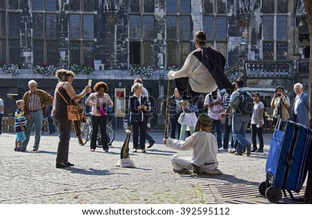 Aachen, Germany - August 28, 2013: Street artists perform a fakir trick on the town square while spectators watch in Aachen, Germany on August 28, 2013 - stock photo