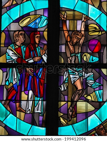 AACHEN, GERMANY - MAY 8, 2010: Stained glass window depicting Jesus Christ on the cross in the Dom of Aachen, Germany.  - stock photo