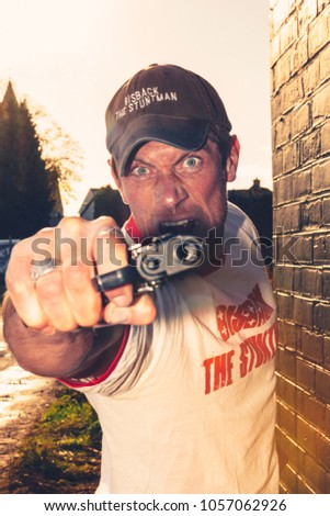 Aalst, Belgium - March 11, 2012: professional stuntman acting in a film holding a gun