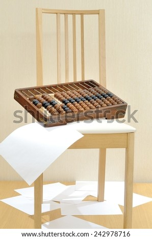 Abacus for accountants, lying on a chair and scattered sheets of white paper - stock photo