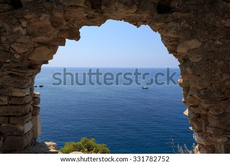 Abandoned ancient ruined wall with hole and view to the sea - stock photo