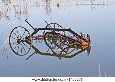 Abandoned antique Side Thresher in flooded field - stock photo