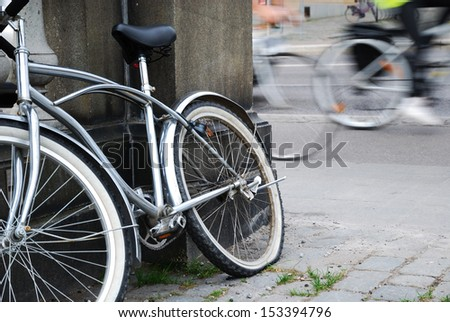 Abandoned bicycle is photographed against the blurred background of moving cyclists. It is leaned against concrete wall lonely. - stock photo