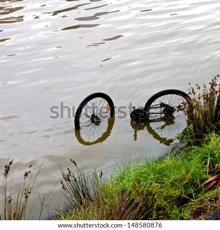 abandoned bicycle lies upside down in a river or creek - stock photo