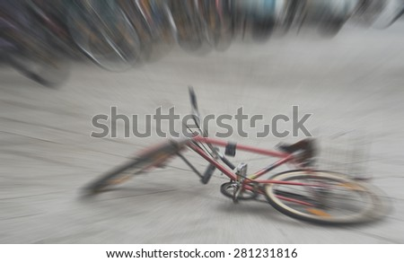 Abandoned broken bike laying on the ground in the middle of the city, defocused with radial zoom, instagram retro washed filter applied in postprocessing - stock photo