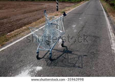 Abandoned broken shopping cart  in a street campaign. Concept -Crash: Consumption crisis - stock photo
