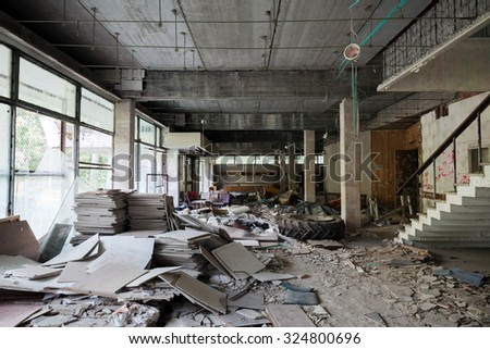 Abandoned building interior. Corridor perspective with dirt on the floor and broken windows - stock photo