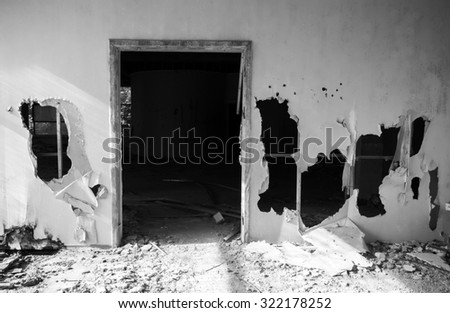 Abandoned building interior. Empty door and holes in wall. Black and white photo - stock photo