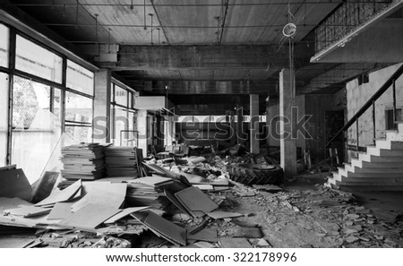 Abandoned building interior. Entrance hall perspective with stairs and broken constructions. Black and white photo - stock photo