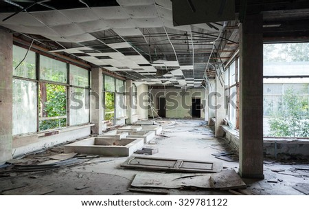 Abandoned building interior. Hall perspective with dirt on the floor - stock photo