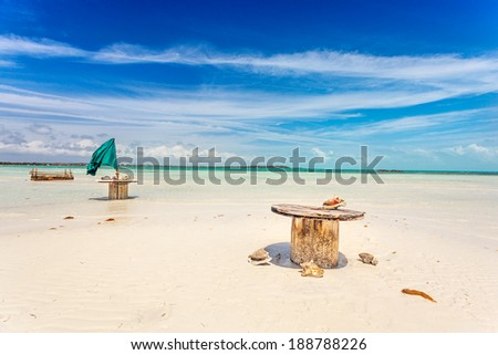 Abandoned cable drum tables on white sand beach near Five Cays, Providenciales, Turks and Caicos - stock photo