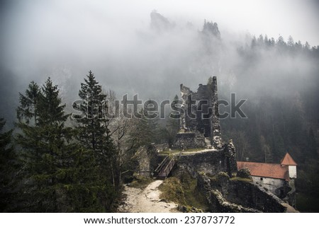 Abandoned Castle Ruins in the Misty Forest with hills behind. Photograph was taken on a gloomy and foggy autumn afternoon. - stock photo