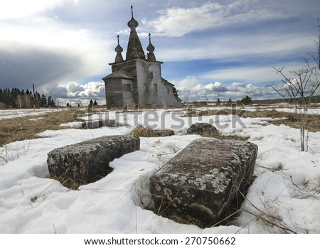 Abandoned cemetery and wooden church (Russia, Arkhangelsk region) - stock photo
