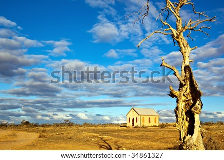 Abandoned church in the desert, in sunset light.  Dead tree in foreground.  Silverton, New South Wales, Australia. - stock photo