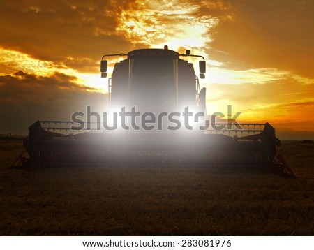 Abandoned combine harvest wheat with lighted main lights in the middle of a farm field. Morning yellow wheat field on the sunset cloudy orange sky background. - stock photo