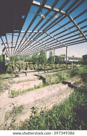 abandoned country farm building in bright summer sun in latvia - vintage film effect - stock photo