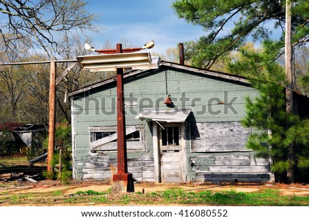Abandoned country store sits with boarded up windows and rusting sign post.   - stock photo