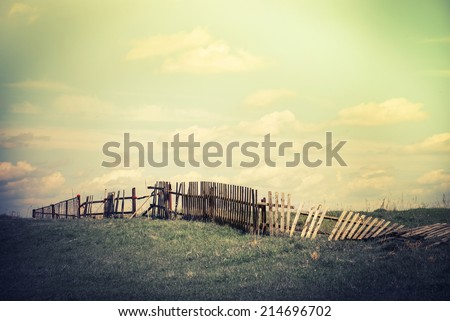 Abandoned countryside. Concept summer landscape with old broken fence at pasture under cloudy sky. Nature background in vintage style - stock photo