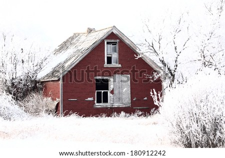 Abandoned dilapidated farm house in winter - stock photo