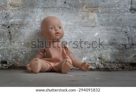 Abandoned doll sitting on a concrete floor - stock photo
