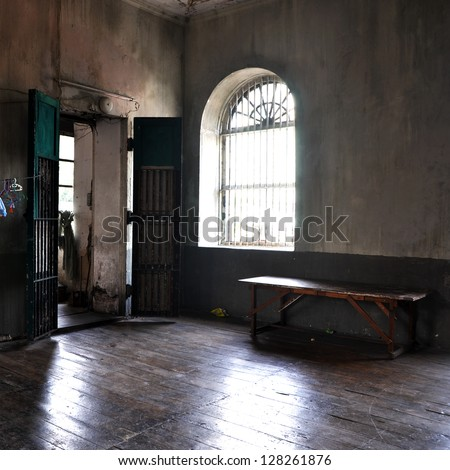 Abandoned empty room with door, window and bench - stock photo