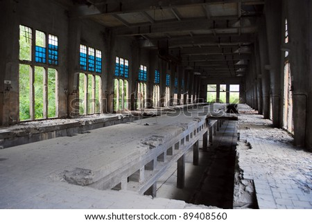 Abandoned factory room, with broken windows. - stock photo