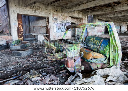 Abandoned factory with a truck chassis spray painted with graffiti. - stock photo