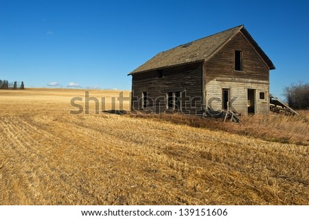 Abandoned farmhouse in a harvested grain field - stock photo