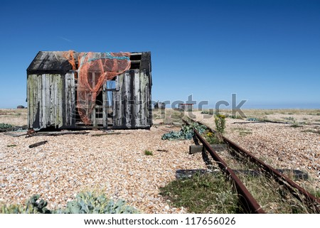 abandoned fishing hut or shed. old wooden cabin on south coast of england in Dungeness - stock photo