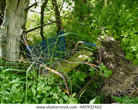 Abandoned grungy retro damaged old metal chair left out in a forest - stock photo