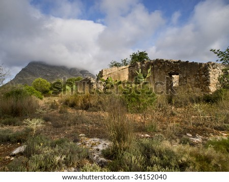 Abandoned house in a Mediterranean forest with some typical vegetation and a beautiful cloudy sky
