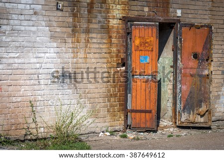 Abandoned industrial brick wall with an old wooden open garage gate - stock photo