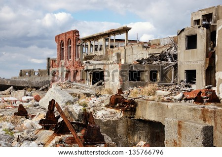 Abandoned island of Gunkanjima off the coast of Nagsaki, Japan. The island was populated as a coal mining town from 1887 but was abruptly abandoned in 1974 due to the rise of petroleum use. - stock photo