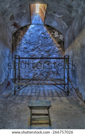 Abandoned Jail Cell with Bed and Stool - stock photo