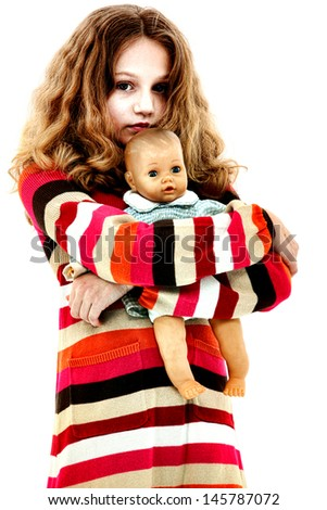 Abandoned lonely child hugging doll.