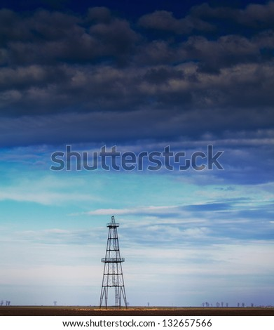Abandoned oil rig profiled on cloudy day sky - stock photo