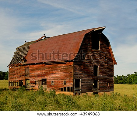 Abandoned old barn surrounded by beautiful blue sky with two crows perched on top of the decaying wooden structure. - stock photo